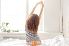 Back view of relaxed female in pyjamas, stretches hands, sits on royalty free stock photography