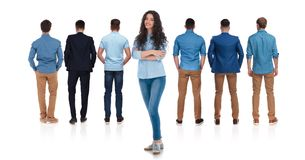 Back view of relaxed group of men and woman leader. Back view of relaxed group of men standing on white background with hands in pockets and casual women leader royalty free stock image