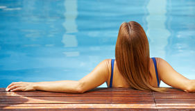 Back view of relaxed woman in pool Stock Photos