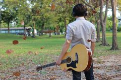 Back view of relaxed young man with headphones is holding acoustic guitar and falling leaves in outdoor park. Back view of relaxed young man with headphones is Stock Photo