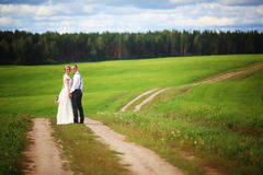 Back view of romantic couple of bride and groom walking hand in hand on rural road. Stock Photo