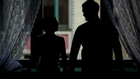 Back View of Romantic Couple Standing near the Window in the Darkness. Man is Taking Woman Hand in His, They are Kissing stock video footage