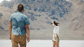 Back view romantic couple walk together holding hands towards epic white flat land in the middle of Utah salt desert. stock video