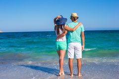 Back view of romantic couple at white beach during Royalty Free Stock Images