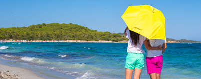 Back view of romantic couple at white beach with. Back view of young couple walking at beach during tropical vacation in Sardinia Royalty Free Stock Images