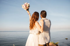 Back view of a romantic happy married couple standing. At the beach Stock Images