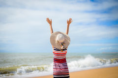Back view of romantic lady enjoying summer beach and sun, waving at sea. Stock Photo