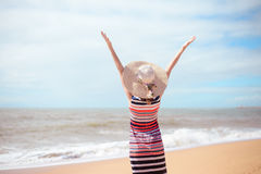 Back view of romantic lady enjoying summer beach and sun, waving at sea. Concept of feeling and freedom Stock Image