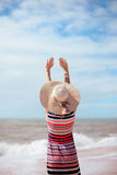 Back view of romantic lady enjoying summer beach and sun, waving at sea. Concept of feeling and freedom Royalty Free Stock Photos