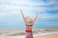 Back view of romantic lady enjoying summer beach and sun, waving at sea. Concept of feeling and freedom Stock Photography