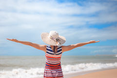 Back view of romantic lady enjoying summer beach and sun, waving at sea. Concept of feeling and freedom Royalty Free Stock Photography