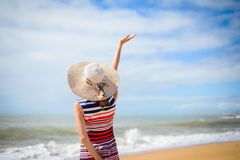 Back view of romantic lady enjoying summer beach and sun, waving at sea. Concept of feeling and freedom Royalty Free Stock Images