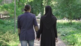 Back view of romantic muslim couple walking in park and talking. Camera follows loving bearded man in suit and young