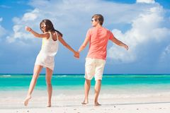 Back view of romantic young couple holding hands on the beach Royalty Free Stock Photo