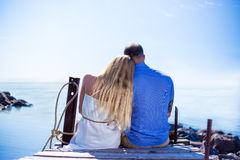 Back view of romantic young couple sitting on the pier Stock Image