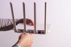 The back view of router showing the lan internet port, and the hand is plugging in the land cable on a white router Royalty Free Stock Image