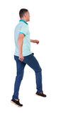 Back view of running man in blue polo. Royalty Free Stock Photography
