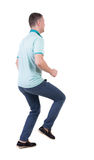 Back view of running man in blue polo. Royalty Free Stock Photo