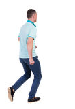 Back view of running man in blue polo. Royalty Free Stock Images