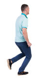 Back view of running man in blue polo. Stock Image