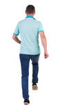 Back view of running man in blue polo. Stock Photography