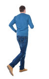 Back view of running man in blue pullover. Royalty Free Stock Photos