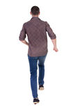 Back view of running man in brown shirt. Royalty Free Stock Photo