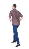 Back view of running man in brown shirt. Stock Photos