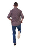 Back view of running man in brown shirt. Royalty Free Stock Photography