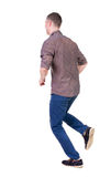 Back view of running man in brown shirt. Stock Photo