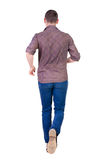Back view of running man in brown shirt. Royalty Free Stock Photos