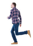 Back view of running man in checkered shirt. Royalty Free Stock Images