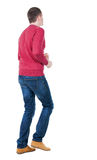 Back view of running man in redpullover. Stock Photo