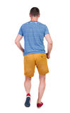 Back view of running man in t-shirt and shorts Stock Photos