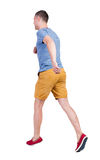 Back view of running man in t-shirt and shorts Stock Photo
