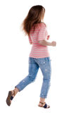 Back view of running  woman. beautiful redhead girl in motion. Stock Photo