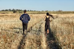 Back view of running woman and man training in field, jogging. Woman and men training in field, jogging back view. Two young athletic people running in royalty free stock photography