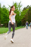 Back view of running woman in park. Process is important. Youthful woman is practicing running in green park Royalty Free Stock Image