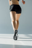 Back view of running woman in sportive clothing. On grey Royalty Free Stock Photography