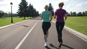 Back view of running women jogging in the park stock video footage