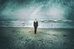 Sad blonde woman walks alone on sandy beach. Back view of a sad blonde woman walks alone on sandy beach. Grunge filter effect used Royalty Free Stock Images