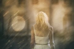 Sorrow blonde woman background. Back view of a sad sorrow blonde woman lower her head at rainy day with magic sunlight. Selective focus used Stock Photo