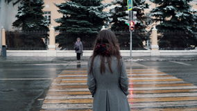 Back view. The sad young brunette girl is waiting the green light to cross the road in a winter snow-covered city. Back view. The sad young attractive brunette stock video