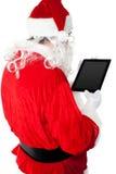 Back view of Santa looking at tablet device screen Royalty Free Stock Photo