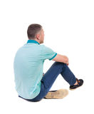 Back view of seated handsome man in polo looking up. Stock Photos