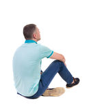 Back view of seated handsome man in polo looking up. Royalty Free Stock Photos