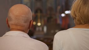Back view of senior couple sitting in catholic church. Two pensioners ceremony service praying stock video footage