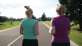 Back view of senior fitness women running on road stock video footage