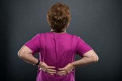 Back view of senior lady doctor holding back like hurting. On black background with copyspace advertising area Royalty Free Stock Images