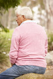 Back View Of Senior Man Sitting On Wall Royalty Free Stock Photography